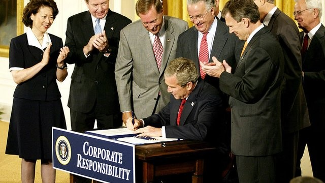 president george bush signing an official document at a table that says corporate responsibility. congress members clap around him